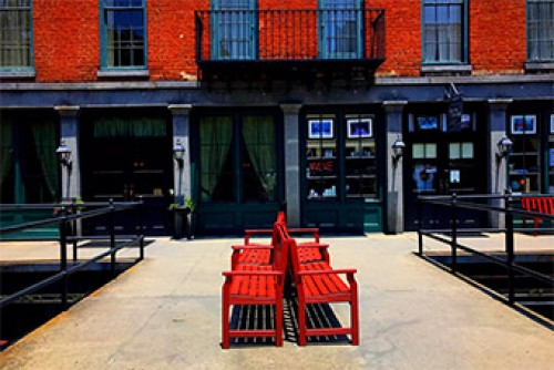 Photograph of four red colored benches on an outdoor sidewalk.